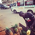 Selling pinepaples in a Kampala Market while a tax Van conductor calls out for passengers to board.jpg