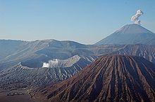 Meze maldekstre la vulkano Bromo. En la fono dekstre la plej alta monto de Javo, la vulkano Semeru. Malfone dekstre la Batok