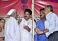 Shri A.T. (Nana) Patil, Member of Parliament Jalgaon, presenting hearing aids to an old man, during the Public Information Campaign, at Chalisgaon, Dist Jalgaon, Maharashtra on September 10, 2015.jpg