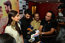 Khan and Sonam Kapoor in front of a bank of microphones and cameras