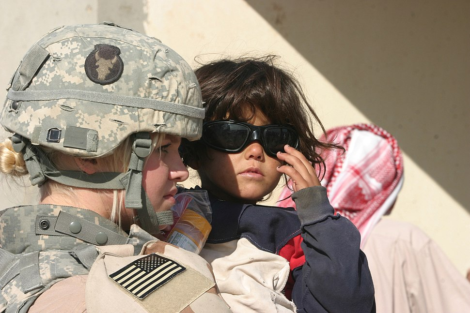 Spc. Taryn Emery attached to 2nd Battalion, 136th Infantry Regiment, holds a local girl who tries on Emery's ballistics glasses during a combined humanitarian, medical, school and hygiene engagement