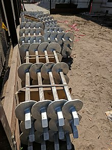 photo of a stack of helical anchors at a construction site