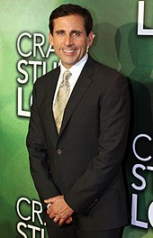 The image is of actor Steve Carell. He is standing in front of a green background, wearing a suit, and smiling.