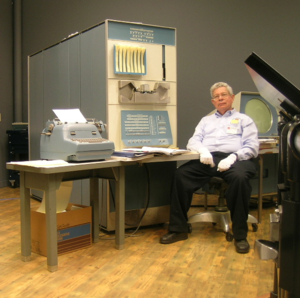 PDP-1 - PDP-1 at the Computer History Museum with  Steve Russell, creator of Spacewar!. The large cabinet houses the processor itself. The main control panel is just above the desk, the paper tape reader is above it (metallic), and the output of the Teletype model BRPE paper tape punch above that (vertical slot). A storage tray for eight fanfold paper tapes is attached to the top panel. At the left is the IBM Model B typewriter modified by Soroban, and the Type 30 CRT display is to the far right.
