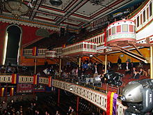 A view away from the stage shows painted front edges of two balconies and the decorated ceiling.
