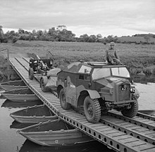 Photograph of a complete 25 pounder gun, limber and 'Quad' tractor crossing a bridge (in the British Isles)