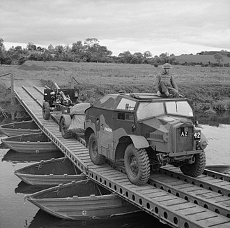 "Ordnance QF 25-pounder - A 25-pounder field gun and limber, towed by a Morris Commercial ""Quad"", crossing a pontoon bridge at Slaght Bridge in Antrim, Northern Ireland, 26 June 1942"