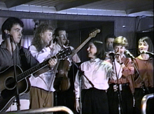 The Rankin Family performing aboard the M/S Scotia Prince, April 18, 1990. From left to right: Jimmy Rankin, Natalie MacMaster, Bruce Phillips, Raylene Rankin, John Morris Rankin, Cookie Rankin, Heather Rankin.