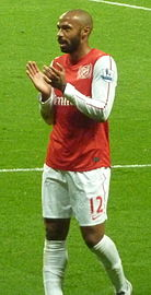 Thierry Henry, wearing a red shirt with white long sleeves and shorts with a number 12 and Nike logo on the left-leg side, applauds.