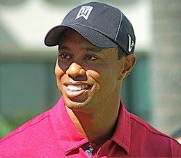 Devant une large foule réunie autour d'un green de golf, un joueur lève les bras.