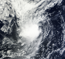 A visible satellite image showing a poorly-organized tropical storm, with its center of circulation exposed, on October 14.