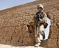 U.S. Marine Corps Cpl. Michael Emerson, a designated marksman with the 1st Platoon, Fox Company, 2nd Battalion, 2nd Marine Regiment, steps through the wall of a compound while searching for signs of insurgency 130729-M-DE426-011.jpg