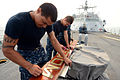 U.S. Navy Boatswain's Mate Seaman Ricky Jones, front, and Operations Specialist Seaman Kyle Kiner, assigned to the littoral combat ship USS Freedom (LCS 1), polish the ship's sign as the ship pulls 130615-N-PD773-063.jpg