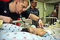 U.S. Navy Lt. Thom Miller, left, checks the vitals of a four-month-old Indonesian girl who had surgery to fix her cleft lip aboard Military Sealift Command hospital ship USNS Mercy (T-AH 19) in North Sulawesi 120602-O-ZZ999-006.jpg