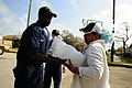 U.S. Navy Machinist's Mate 2nd Class Kevin Paulk, assigned to amphibious assault ship USS Nassau (LHA 4), delivers ice to a resident during a food convoy to the neighborhoods affected by Hurricane Ike 080921-N-KD705-156.jpg