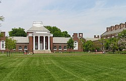 A brick neoclassical building topped by a dome and fronted by four white columns, with a green lawn in the foreground