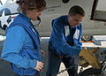 US Navy 040421-N-9742R-001 Airman Elizabeth Vestal, of Lisle, Ill., supervises Airman Jesse Burd, of Spartansburg, S.C., as he uses a tie-down chain to secure the landing gear on an E-2C Hawkeye.jpg