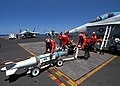 US Navy 040702-N-4190W-001 Aviation Ordnancemen assigned to the Blue Blasters of Strike Fighter Squadron Three Four VFA-34 upload a practice bomb to an F-A-18 Hornet aboard the aircraft carrier USS John F. Kennedy CV 67.jpg