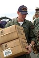 US Navy 050111-N-4383M-170 Gas Turbine System Technician 3rd Class Adam Knuth, assigned to Assault Craft Unit Five (ACU 5), helps unload pre-packaged humanitarian rations.jpg