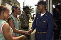 US Navy 050202-N-4047W-016 Chaplain Lt. Cmdr. Carl Farmer, assigned to USS Emory S. Land (AS 39), shakes hands with schoolteachers from Orphia's College in Douala, Cameroon.jpg