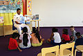 US Navy 051105-N-5006P-025 Navy Recruiter, Electrician's Mate 2nd Class Adam Tobias, reads the book Dino Sailors to a group of young children at the main branch of the San Antonio Public Library.jpg