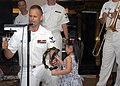 US Navy 070804-N-7706C-001 A girl from Smarter Brunei School for Autistic Children joins Musician 3rd Class Daniel Hassenritter of the U.S. 7th Fleet's Orient Express Band in singing to more than 200 Brunei residents.jpg