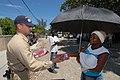 US Navy 070907-N-8704K-134 Senior Chief Sonar Technician Surface Scott Pageau gives a woman a pair of sandals donated by Project Handclasp at Centre de Sante, a health-training center in Croix-des-Bouquet, Haiti.jpg