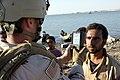 US Navy 080711-M-1391M-016 A boy watches as Gunner's Mate 2nd Class Shawn Sass, assigned to Riverine Squadron (RIVRON) 3, performs a biometrics scan on a fisherman on the Watah Peninsula, near Rawah, Iraq.jpg