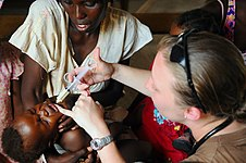 US Navy 080920-N-4515N-371 Lt. j.g. Meagan Murphy, a medical augmentee embarked aboard the amphibious assault ship USS Kearsarge (LHD 3), gives de-worming medication to a child during disaster relief efforts in Haiti.jpg
