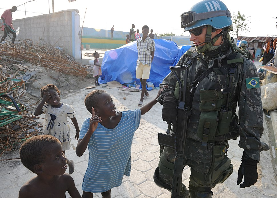 US Navy 100316-N-9116F-001 A Brazilian U.N. peacekeeper walks with Haitian children during a patrol in Cite Soleil