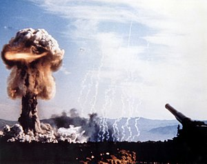 An artillery piece with a mushroom cloud rising in the distance