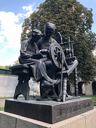 Lithuanian book smugglers - Sculpture showing mother teaching her child from the banned literature near the spinning wheel