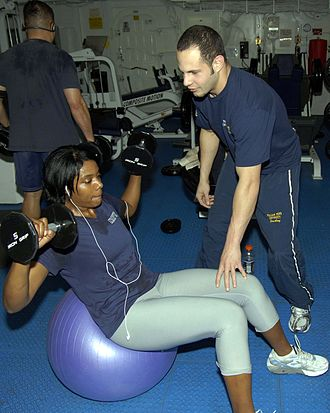 Exercise ball - A woman performing weighted sit-ups on an exercise ball.