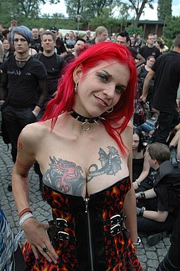Woman with chest tattoos, spiked collar, and fuchsia hair (2007)
