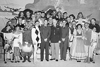 Johnny Gilbert - Gilbert with the cast of Xanadu: The Marco Polo Musical (1953). Gilbert is the fourth person from the left—in the diamond-pattern costume, next to composer William P. Perry.