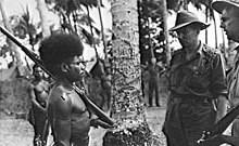 A shirtless Papuan man stands at attention with rifle at slope. Two Australian soldiers wearing shirts and slouch hats stand facing him.
