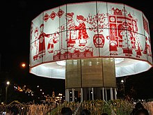 Uma grande faixa redonda de tecido branco decorada com figuras vermelhas e imagens para Tết