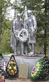 Воины, мужчина и женщина со знаменем преклонившись возлагают венок. Братская могила военнослужащих Красной Армии погибших в годы Великой Отечественной войны (1942 - 1943)