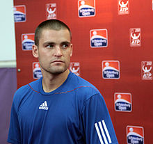 A close to bald man, wearing a blue T-shirts with a white Adidas logo, standing in front of a wall with a dusin St. Petersburg Open logos