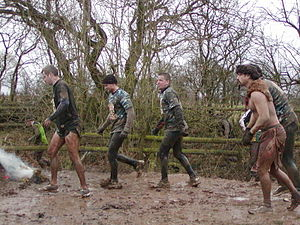 "Tough Guy Competition - ""Tough Guy"" competitors running through mud"
