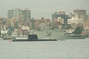 A submarine sitting in calm water, in front of a large warship, and with numerous tall buildings in the background. White uniformed personnel are standing on the decks of both vessels.