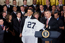 Two men in dark suits stand in front of a crowd in the background and behind a podium in the foreground with the Seal of the President of the United States on it. The two men are holding a white jersey with pinstripes and the number 27 on it.