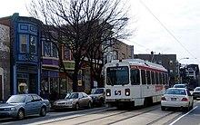 Un carro de un solo coche blanco en la calle.  El estacionamiento en la calle combinado con una vía doble en una calle de dos carriles deja un espacio limitado para la maniobrabilidad del automóvil.
