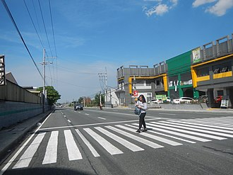 Pedestrian crossing - A woman at a crossing in Carmona, Philippines