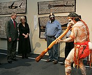 Aboriginal man performing on the Digeridoo indoors with 4 people watching, aboriginal paintings can be seen on the wall behind him