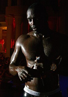 A shirtless black man in a dimly lit area, drenched in sweat