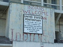"A sign that reads United States Penitentiary has graffiti above it saying ""Indians Welcome""."