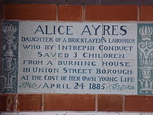 A tablet formed of six standard sized tiles, bordered by green flowers in the style of the Arts and Crafts movement, with an inscription in green capital letters on a white background