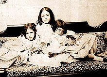 A black-and-white picture of three Victorian children sitting on a couch.