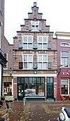 foto van Pand met bakstenen trapgevel versierd met natuurstenen blokken, banden en lijsten, en bekroond door een toppinakel op gebeeldhouwde kraagsteen